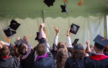 College students throwing caps in the air.
