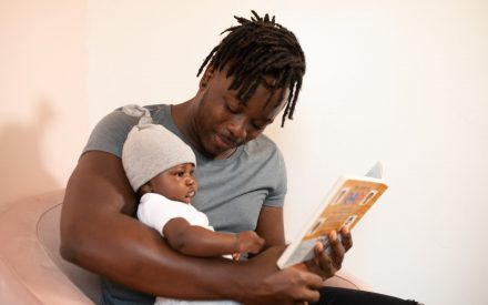 Man sitting on a couch reading to a baby